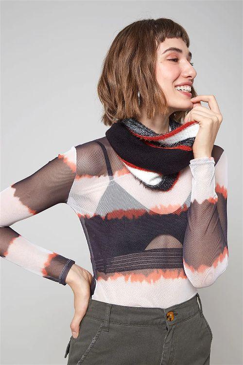 Modelo mulher com a mão direita na cintura e a esquerda no queixo vestindo blusa manga longa tie dye