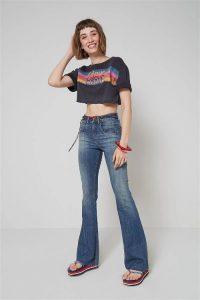 Modelo com a mão na cabeça olhando para frente vestindo calça jeans flare frente menor