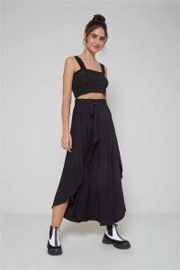 Modelo com pose frontal sorrindo vestido a saia longa com amarração cintura