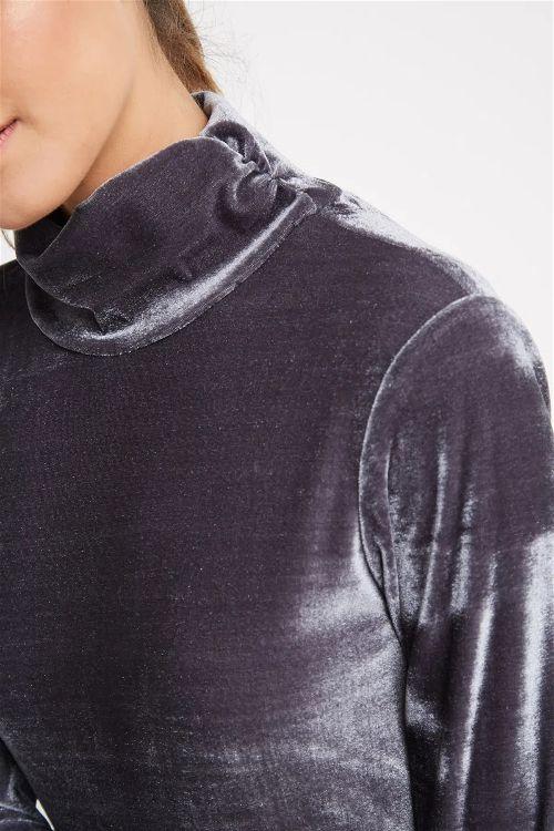 Foto com foco na gola da modelo usando um lusa turtleneck de veludo