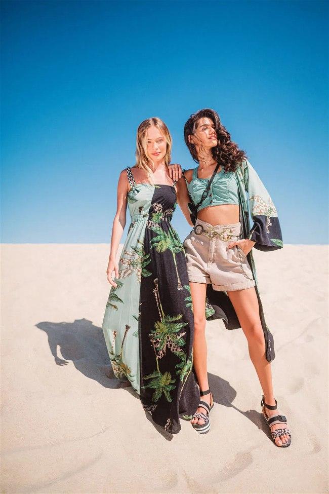 Duas mulheres na areia da praia, uma com vestido e a outra com short e cropped