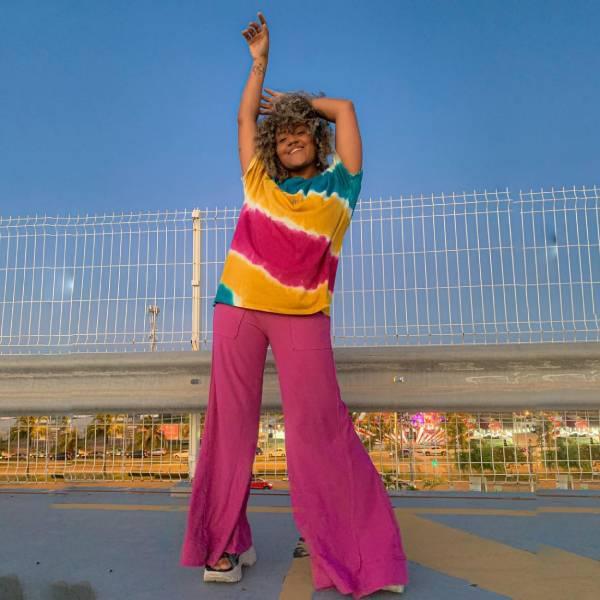 Mulher com roupas coloridas, calça flare rosa e camiseta tie dye
