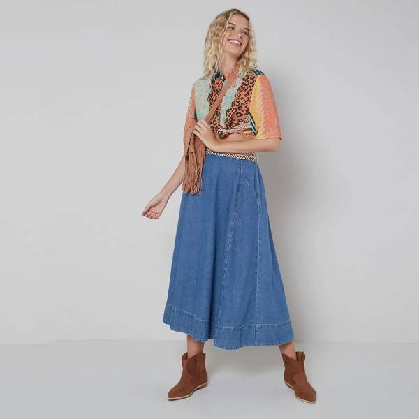 Mulher loira com saia midi jeans, regata e bota